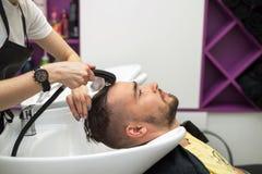 Junger Mann wäscht seinen Kopf in einem Frisörsalon Stockfoto