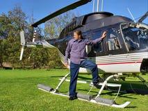 Junger Mann wartet nahe bei kleinem privatem Hubschrauber Stockfotografie