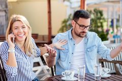 Junger Mann wird gestört, während seine Freundin zu viel Zeit sprechend am Telefon verbringt lizenzfreie stockfotografie