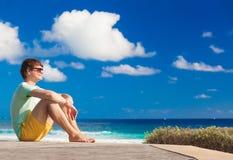 Junger Mann witting nahe dem Strand in Barbados Stockfoto