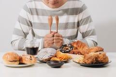 Junger Mann zu Hause auf einer ungesunden Diät stockfotografie