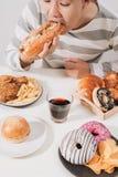 Junger Mann zu Hause auf einer ungesunden Diät lizenzfreie stockfotos