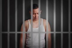 Junger Mann zugeschlossen in Gefängnis lizenzfreie stockbilder