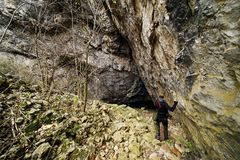 Junger Mann zum Eingang in Cioclovina-Höhle stockfotografie