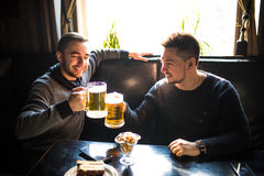 Junger Mann zwei, der im Kneipen-, Essen und Trinkenbier an der Kneipe sitzt lizenzfreies stockfoto