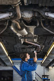Junger Mechaniker, der den Auspuff eines Autos repariert Stockfoto
