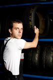 Junger Mechaniker, der Gummireifen im Autoservice erreicht Stockbild