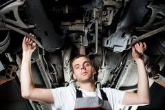 Junger Mechaniker, der unter Auto in der Uniform arbeitet stockfotografie