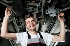 Junger Mechaniker, der unter dem Auto in der Garage arbeitet Stockbild