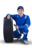 Junger Mechaniker mit dem Reifen, der sich Daumen zeigt Lizenzfreie Stockbilder