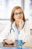 Junger Medizinstudent, der am Schreibtisch im Büro sitzt Stockbild