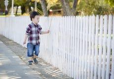 Junger Mischrasse-Junge, der mit Stock entlang weißem Zaun geht Lizenzfreie Stockbilder