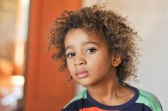 Junger Mischrassejunge mit dem gelockten Haar lizenzfreie stockfotografie