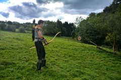 Junger mittelalterlicher Bogenschütze mit Kettenhemd, Pfeil und Bogen in der Natur während des Blattspannens Stockbild