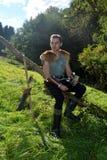 Junger mittelalterlicher Bogenschütze mit Kettenhemd sitzt auf Niederlassung in der Natur im Sonnenlicht, trinkendes Horn im Hand Lizenzfreies Stockbild