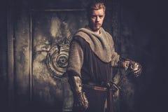 Junger mittelalterlicher Ritter, der auf dunklem Hintergrund aufwirft Stockfotos
