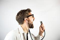Junger männlicher Doktor, der an seinem Stethoskop schreit Lizenzfreie Stockbilder