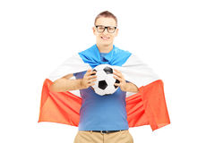 Junger männlicher Fan, der einen Fußball und eine Flagge von Holland hält Stockbilder