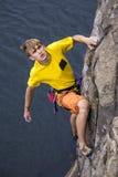 Junger männlicher Kletterer, der über dem Wasser hängt Lizenzfreies Stockfoto