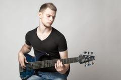 Junger männlicher Musiker, der eine Sechsschnurbass-Gitarre lokalisiert spielt Lizenzfreie Stockbilder