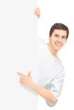 Junger männlicher Patient in einem Krankenhauskleid zeigend auf eine Leerplatte Lizenzfreie Stockfotografie