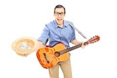 Junger männlicher Straßenausführender mit Gitarre Geld in seinem sammelnd Lizenzfreies Stockbild