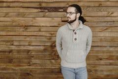 Junger Modebartmann in den Brillen, in den Jeans und im Pullover auf hölzernem Hintergrund Stockfotografie