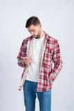 Junger Modemann betrachtet den Schirm des Telefons lizenzfreie stockbilder