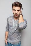 Junger Modemann, der eine Hand auf seinem Hals hält Lizenzfreie Stockbilder