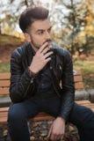 Junger Modemann, der seine Zigarette genießt Stockbilder