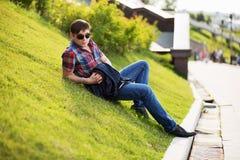 Junger Modemann in der Sonnenbrille, die auf dem Gras sitzt Lizenzfreie Stockbilder