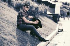 Junger Modemann in der Sonnenbrille, die auf Gras im Stadtpark sitzt Lizenzfreies Stockbild
