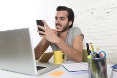 Junger moderner Hippie-Artstudent oder -geschäftsmann, die unter Verwendung des Handylächelns glücklich arbeitet Stockbilder