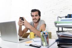 Junger moderner Hippie-Artstudent oder -geschäftsmann, die unter Verwendung des Handylächelns glücklich arbeitet Lizenzfreie Stockfotografie