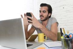 Junger moderner Hippie-Artstudent oder -geschäftsmann, die unter Verwendung des Handylächelns glücklich arbeitet Stockfotografie