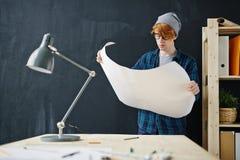 Junger moderner Ingenieur Studying Blueprints lizenzfreie stockfotos