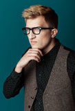 Junger moderner Mann in einem Hemd, in einer Weste und in Gläsern Stockfotografie