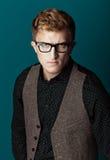 Junger moderner Mann in einem Hemd, in einer Weste und in Gläsern Stockfoto