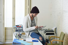 Junger modischer Geschäftsmann im informellen Blick des Beanie und des kühlen Hippies, der auf Hauptschreibtisch unter Verwendung Stockfotografie