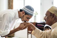 Junger moslemischer Mannvertretungsrespekt zu seinem Vater stockfotografie