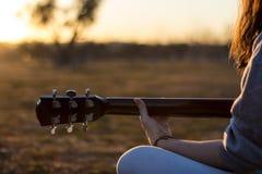 Junger Musiker, der Akustikgitarre an der Dämmerung spielt Lizenzfreies Stockbild