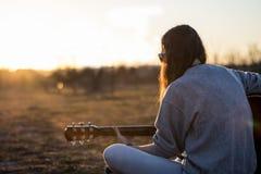 Junger Musiker, der Akustikgitarre an der Dämmerung spielt Stockfotografie