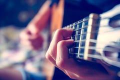 Junger Musiker, der Akustikgitarre spielt Stockbild