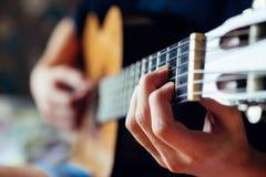 Junger Musiker, der Akustikgitarre spielt Stockfoto