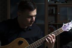 Junger Musiker, der auf Gitarre spielt Lizenzfreie Stockfotografie