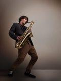 Junger Musiker, der auf Saxophon spielt Lizenzfreies Stockfoto