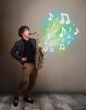 Junger Musiker, der auf Saxophon während musikalische Anmerkungen explodin spielt Stockfoto