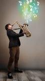 Junger Musiker, der auf Saxophon während musikalische Anmerkungen explodin spielt Lizenzfreies Stockbild