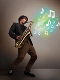 Junger Musiker, der auf Saxophon während musikalische Anmerkungen explodin spielt Stockfotografie