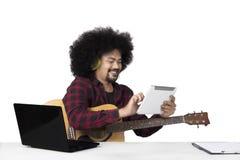 Junger Musiker, der digitale Tablette verwendet Stockbild